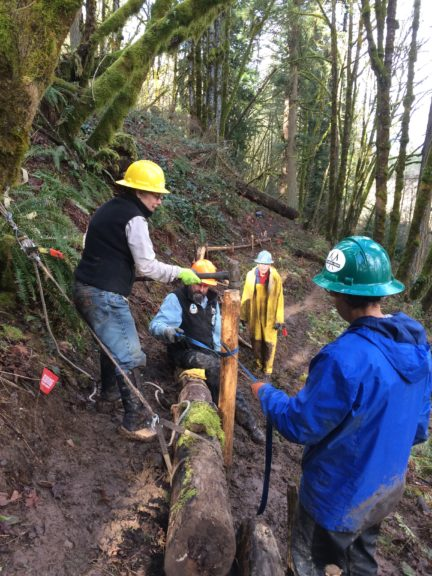 A hard-hatted woman pounds a sledge hammer onto an upright log while two trail workers support the log with straps.