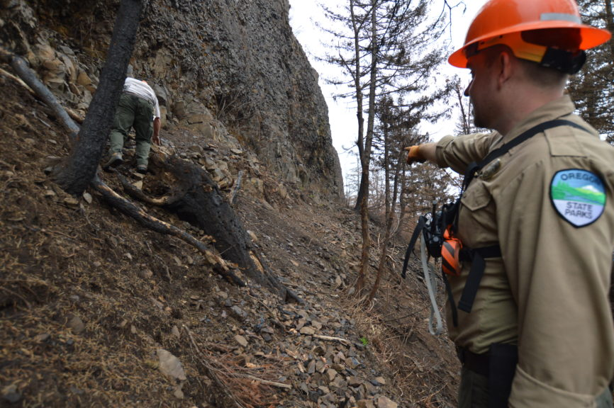 A park ranger points to a sloping rocky trail at the base of a cliff with burnt trees around.